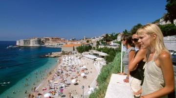 Dubrovnik: giovani ragazze guardano la spiaggia dall'alto per scegliere il prossimo posto al sole (foto:alamy/milestonemedia)