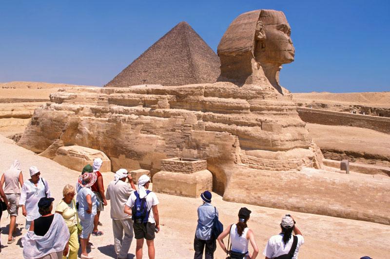 I turisti in visita davanti alla Sfinge, simbolo dell'Egitto, meraviglia architettonica tra le piramidi di Giza (foto: Alamy/Milestonemedia)