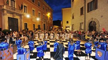 Fra Piazza Olivieri e via Branca a Pesaro va in scena la tradizionale scacchiera vivente: i bambini diventano colorati pedoni in carne e ossa