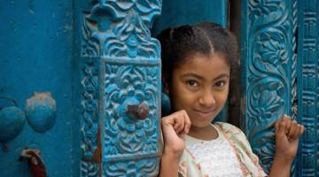 Un sorriso fra le porte tradizionali di Stone Town, la capitale di Zanzibar, dalle tradizionali porte di legno con le cornici in ottone (foto: Alamy/Milestonemedia)
