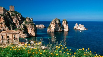 Il mare della Sicilia occidentale invita alla navigazione a vela, con escursioni che costeggiano luoghi d?incanto nel blu, fino alle inconfondibili forme dei Faraglioni della Tonnara di Scopello (foto Alamy/Milestonemedia)