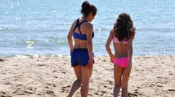 Due bambine passeggiano alla Playa, sulla spiaggia dorata di Catania (foto: Valentina Castellano Chiodo)
