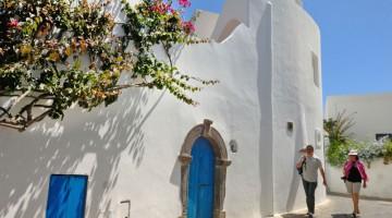 Colori di Panarea: il bianco brillante delle tipiche case eoliane, le porte e finestre sono azzurre, per le vie fioriscono le buganville (foto: Alamy/Milestonemedia)