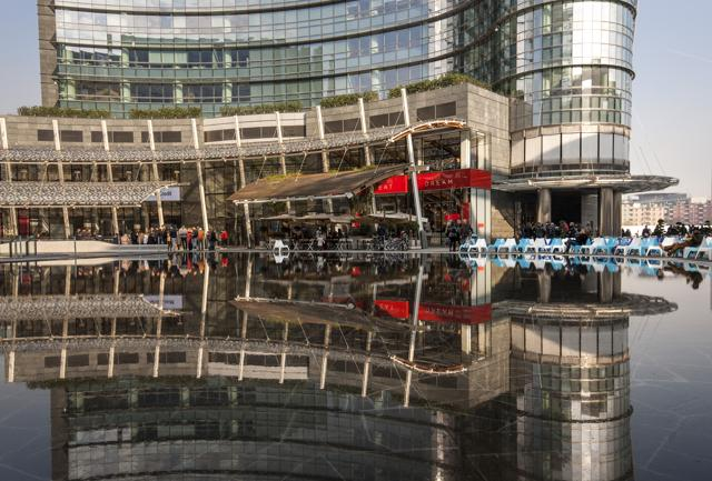 Piazza Gae Aulenti è diventata la nuova agorà meneghina: caffetterie, librerie e store di marchi internazionali si affacciano su 2.300 mq di ardesia, tra fontane e specchi d'acqua (ph: Giovanni Tagini).
