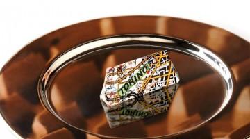 """Il logo ufficiale di Cioccolatò 2012: un gianduiotto avvolto dalla cartina stadale. Il claim è """"O ci vai o ci sei"""""""