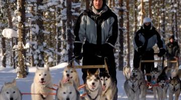 Alcuni musher con le loro slitte, trainate da infaticabili cani husky