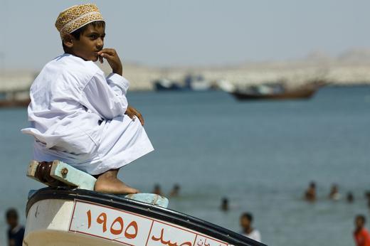 Un bambino omanita con il tipico abito tradizionale, seduto su una barca