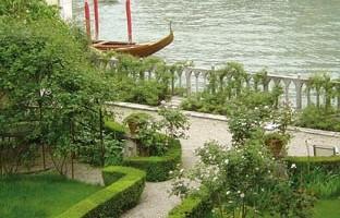 Le curatissime aiuole fiorite e la balaustra in pietra sul Canal Grande del giardino di Palazzo Cappello Malipiero Barnabò
