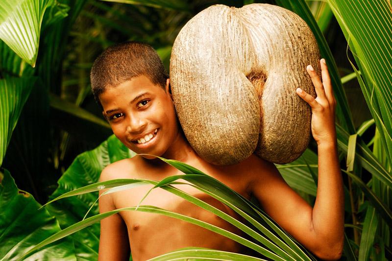 Un giovane abitante trasporta sulle spalle un cocco di mare (foto: Raymond Sahuquet)
