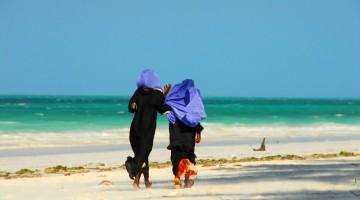 Due donne del luogo passeggiano su una spiaggia di Zanzibar
