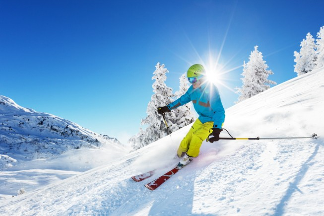 Man skier running downhill on sunny Alps slope