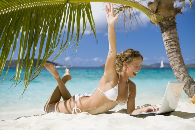 excited woman with her hand raised working on laptop at a tropical beach in the Caribbean