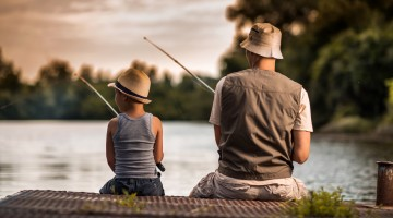 Rear view of a father and son freshwater fishing.