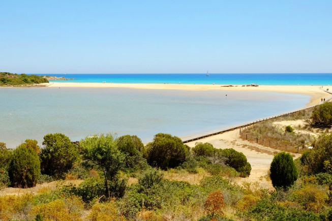 View on the beach Chia with crystal sea water and golden sand in Sardinia, Italy.