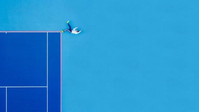 """Primo posto nella categoria """"Persone"""" per Martin Sanchez con una foto dell'alto di un campo da tennis in New Jersey che mostra, da un punto di vista inedito, un tennista che si allena eseguendo degli esercizi a terra"""