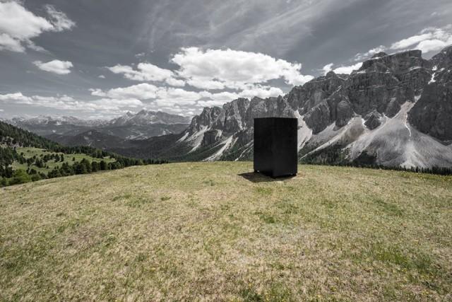 """L'opera """"Der Haps"""" dei due artisti Amin Hak-Hagir e Irene Hopfgartner: un prisma a base quadrata, nero, in cima ad una collina in mezzo a unamalga isolata nella località Munt d'Adagn, nel comune di San Martino"""