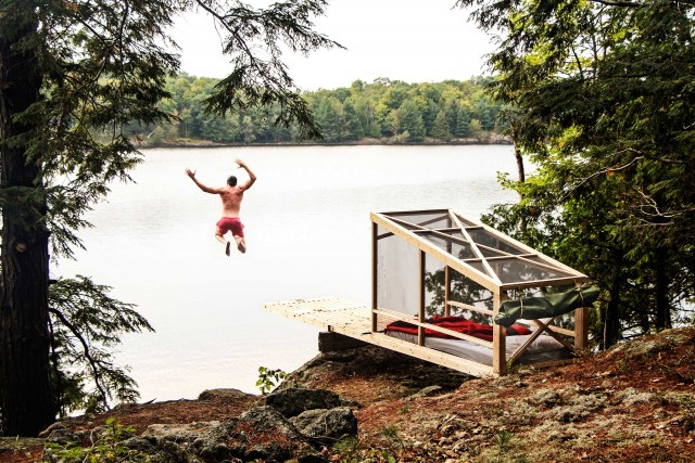"""STUDIO NORTH – ONTARIO, CANADA. Un piattaforma di circa sei metri quadri, completamente ecosostenibile, adatta per la bella stagione, realizzata dagli architetti canadesi di Studio North a Bobs Lake, in Ontario (Canada). """"Una struttura base per dormire e divertirsi"""", sintetizzano i progettisti, che all'interno hanno posizionato un futon a due posti per il sonno. Quando il tempo si fa brutto, basta srotolare una tela cerata per proteggersi. Si affitta su richiesta, contattando studionorth.ca."""