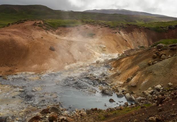 L'area geotermale di Seltún accoglie i visitatori con piccoli crateri rossastri da cui escono sbuffi caldi di vapore sulfureo.
