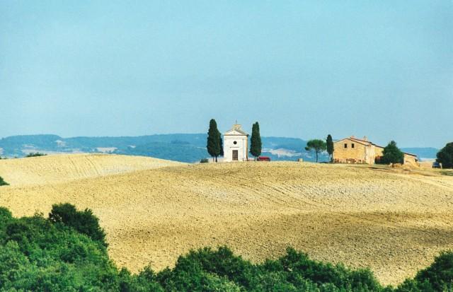 Sullo sfondo, tra i campi arati, ecco la cappella della Madonna di Vitaleta:luogo di culto che si può vedere sulla strada che unisce Pienza a San Quirico d'Orcia.
