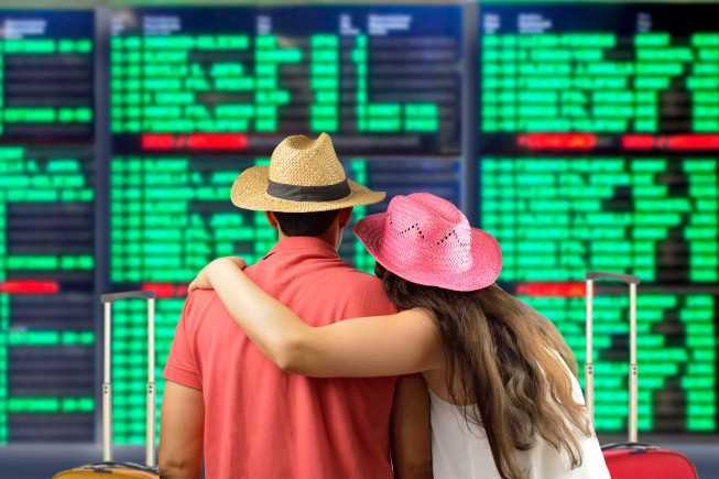 affectionate young couple in international airport looking at the flight information board, checking her flight
