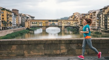Fitness woman jogging in front of ponte vecchio, florence, italy