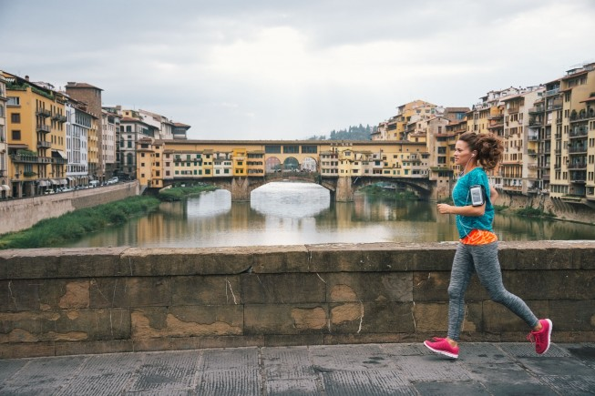 Fitness woman jogging in front of ponte vecchio in florence, italy