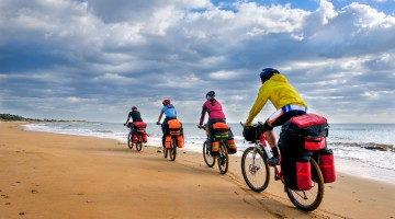 group of cyclists riding sandy beach bike