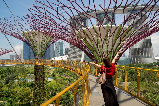 Singapore, Singapore - August 27, 2013: A Japanese tourist poses for a photo on the OCBC Skyway at Gardens by the Bay, Marina Bay, with her arms resembling the shape of the large Supertree structures beside her.