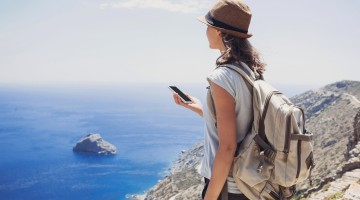 Girl on a hiking trail holding smartphone. Travel and active lifestyle concept