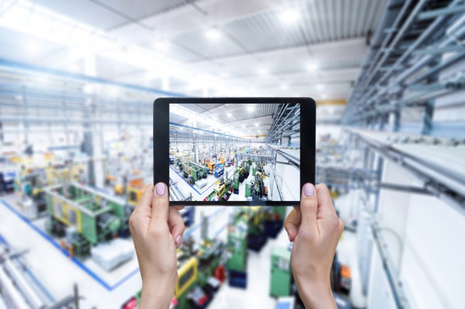 Horizontal color close-up image of female hands holding digital tablet in modern factory. Ordering online from production line on touch screen tablet.