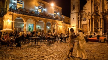 An outdoor restaurant and Salsa dancers on the cobble stoned Plaza Catedral in Old Havana.