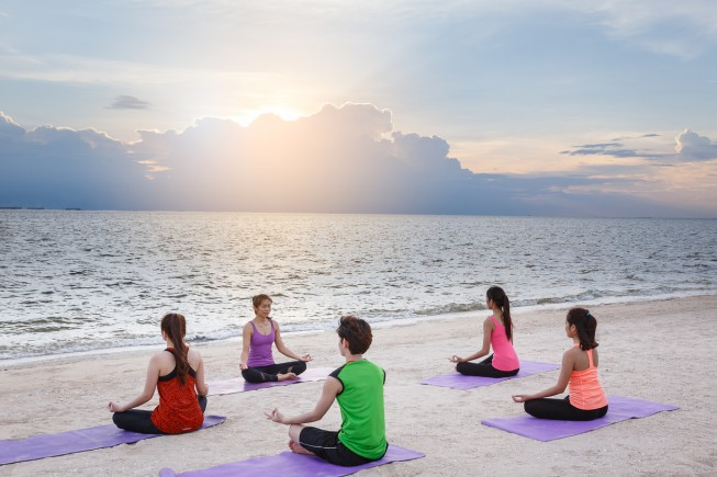 Group of young people practicing yoga on the beach, yoga and healthy lifestyle concept