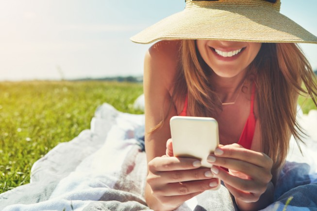 Shot of a cheerful young woman wearing a hat while lying on the ground busy with her phone outside in the sun