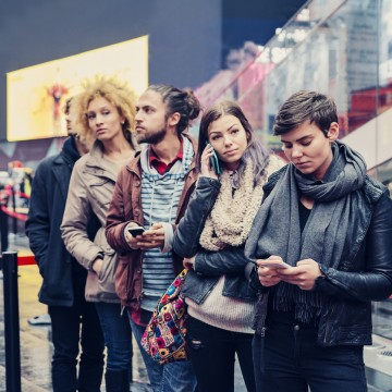 Young people waiting in line to buy tickets in New York. While waiting they are on the phone or texting. Blank placard on the right. Focus on the girl with short hair. It's raining lightly and they are in Times Square. Waist up outdoors horizontal shot.