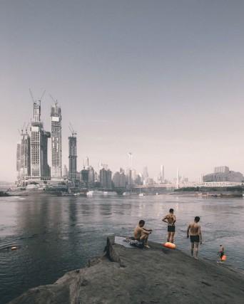 A Chongqing, in Cina, nel punto dove confluiscono i fiumi Yangtze e Jialing, sta nascendo Raffles City. Le sue torri, progettate dall'architetto Moshe Safdie, si ispirano alla lunga tradizione commerciale della città. Zhu Wenqiao ha fotografato alcune persone che fanno il bagno sulla riva opposta.