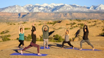 A group yoga class at sunset on the red rocks of Moab, Utah USA.