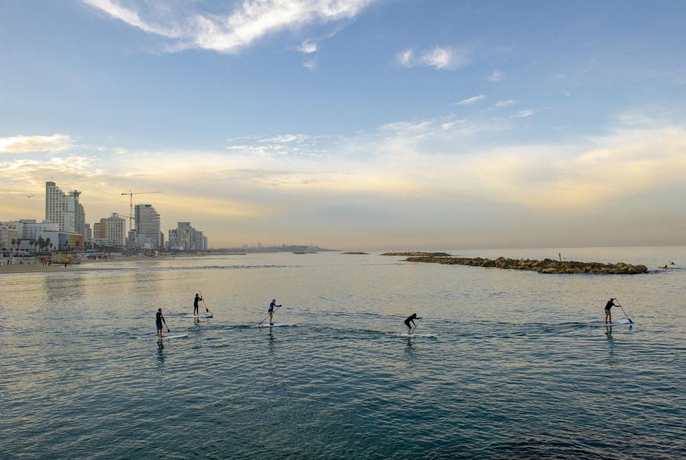 Il Tayelet di Tel Aviv si anima fin dalle prime ore del mattino, con i locali che vi praticano ogni tipo di sport - qui, un piccolo gruppo che pratica Stand Up Paddling