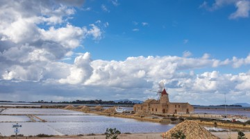 Marsala,Trapani, Sicily. February, 11 2018: Sicilian salt lakes with wind mills, during a sunny day with cloudy sky.