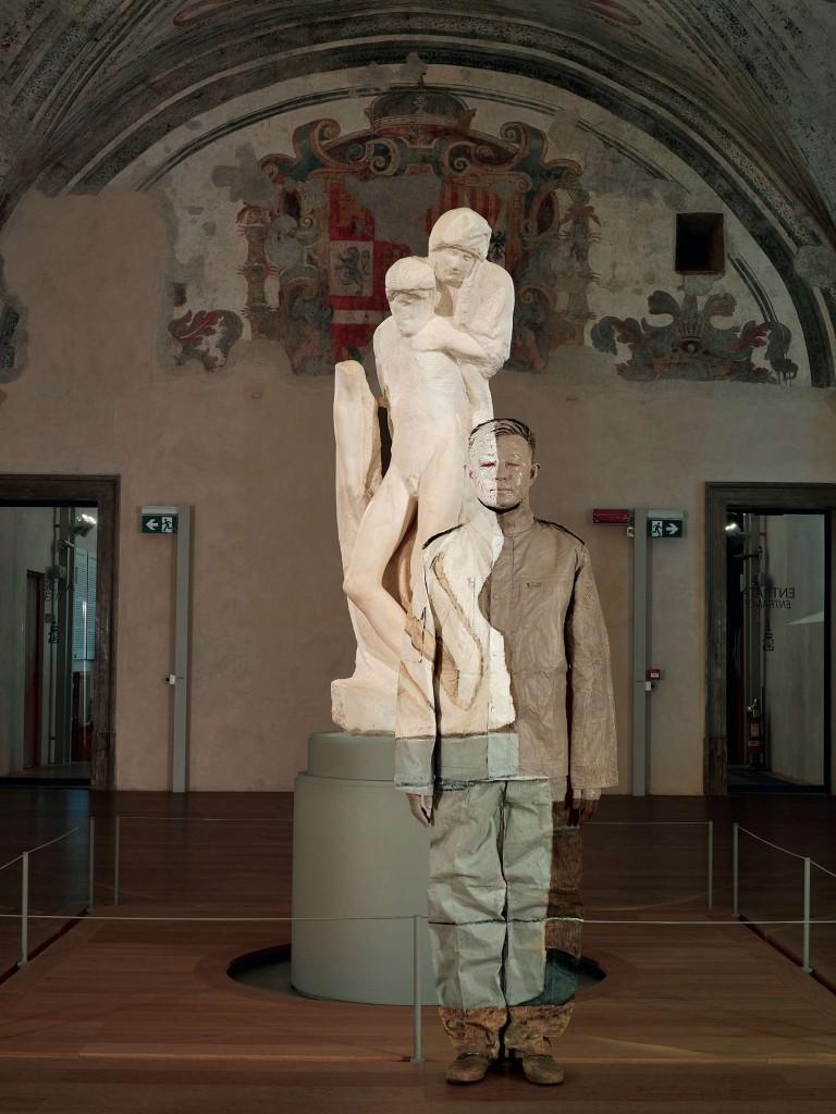 Liu Bolin: camuffamento davanti alla Pietà Rondanini di Michelangelo,  nel Cortile delle Armi del Castello Sforzesco,  nel Cortile delle Armi del Castello Sforzesco, allestita nel Cortile delle Armi del Castello Sforzesco.