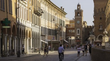 A city street in central Ferrara in the Emilia-Romagna region of Italy. At the end of the street stands Torre dell'Orologio, a historical clock tower.