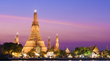 The illuminated temple of Wat Arun on the Chao Phraya river at sunset in Bangkok, Thailand