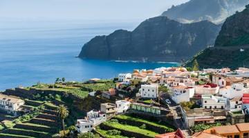 Village at Atlantic ocean shore and high rocks.
