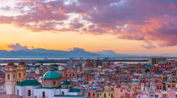 Sunset on Cagliari, evening panorama of the old city center in Sardinia Capital, view on The Old Cathedral and colored houses in traditional style, Italy.