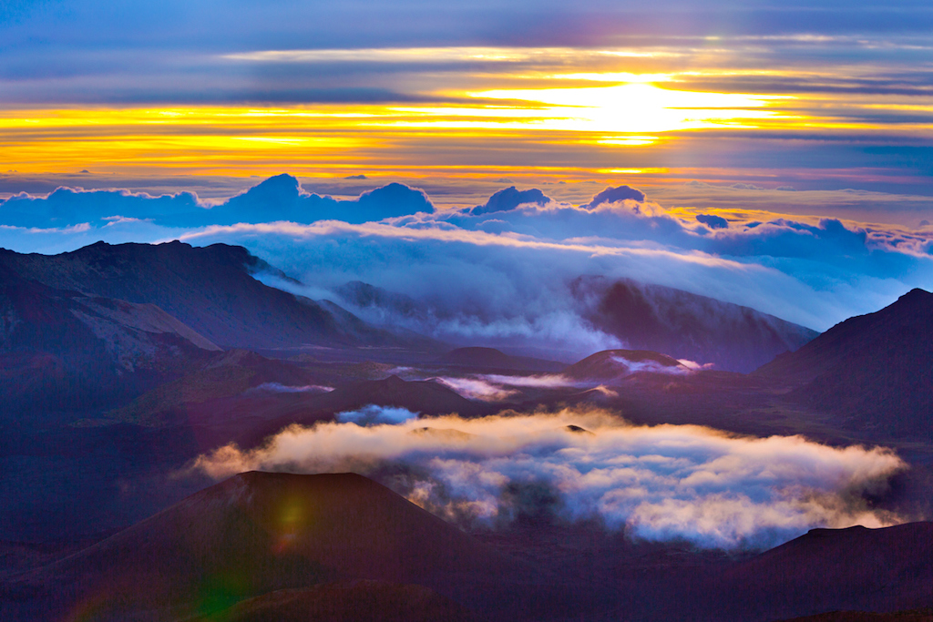 The sunrise in the Haleakala Crater in Maui, Hawaii. A volcanic crater on the peak of the Haleakala Volcano on top of the island of Maui. Over 10,000 feet above sea level, an incredible view from the crater at sunrise. A popular tourist destination all day, especially at sunrise and sunset. Photographed in horizontal format.