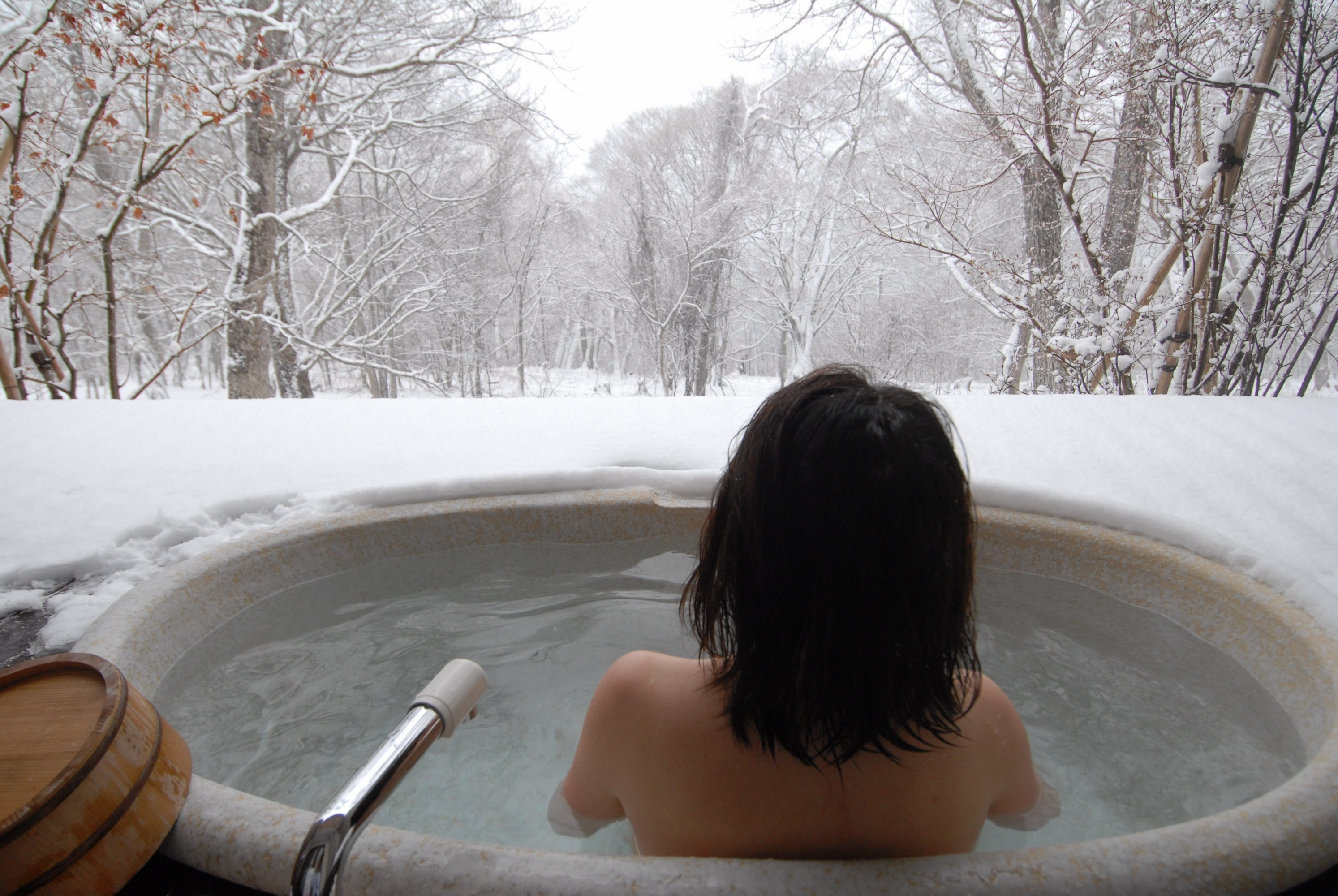 young Japanese woman in a hot open air bath while snowing