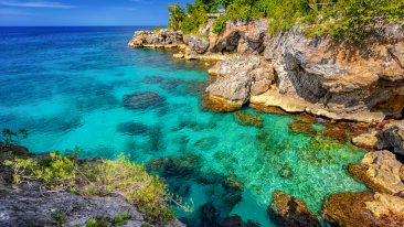 Beautiful clear turquoise water near rocks and cliffs in Negril Jamaica. Caribbean paradise island and water at the seaside with a blue sky and nice day light