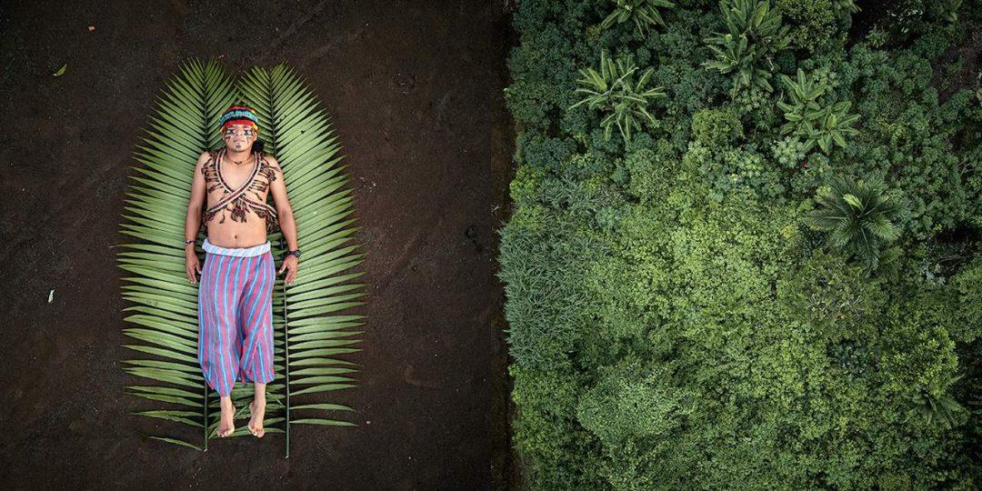 """Nella serie vincitrice """"Seeds of Resistance"""" l'istantanea del giovane indigeno Nantu, che gestisce i traghetti a energia solare in Ecuador, e a destra la sua casa, la foresta pluviale di Achuar (ph: Pablo Albarenga)"""